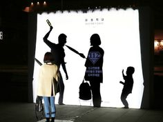 In South Korea is a brightly lit billboard that features the silhouettes of a young child threatened by a man holding a glass bottle.
