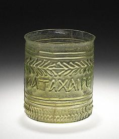 """Roman Glass Beaker with Greek Inscription, c. 1st Century CE. Made from greenish-transparent glass, this small beaker or cup features several decorative bands including a wreath pattern, and near the base, a row of chevrons. Below the wreath, an inscription in Greek suggests the beaker's festive function: """"rejoice and be merry."""""""