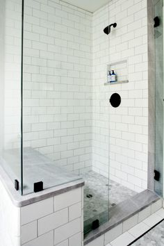 This walk-in shower has the space to let you shower in luxury. White tile walls are revealed through the glass surroundings. A gray tile floor complements the gray-topped bench allowing for seating. A black shower head and knob bring a dark pop of contrast color to the white.