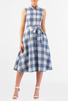 Our cotton check shirtdress is capped with a mandarin collar and the seamed waist nips in the silhouette above a full flare skirt that gently swishes as you move.