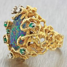 Collectors Coins & Jewelry ITEM DESCRIPTION This is a Vintage Art Deco Style 18k Gold Blue Dublet Fire Opal Diamond & Emerald Modernist Cocktail Ring. This ring is a size 6.5 and could be re-sized. Please contact us for details. It will come professionally packaged in a beautiful ring presentation box and our 2 week unconditional money-back guarantee.Stone Details;- Stone Type: Blue Fire OpalStone Cut: OvalStone Count: 1Stone Measurements: 17.5mm X 13.5mmStone Type: DiamondsStone Cut: Round…