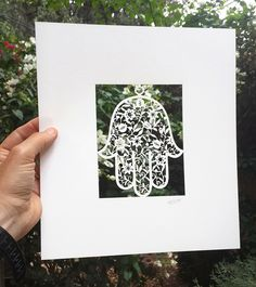 """Ready for framing, this stunning work of art will draw gasps of wonder from all who behold it! It is an original design by Jerusalem artist David Fisher in which the laser cut paper results in an incredibly ornate floral pattern inside the traditional Hamsa shape. Laser-Cut Paper  Size: 11"""" X 9.78""""   David Fisher, born in Jerusalem, is an Israeli graphic designer who has revived the traditional Je"""