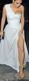 Kim Kardashianstruggled to contain her incredibly ample assets as she hoists her sexy white gown up following romantic meal in Rome with husband Kanye West on Sunday evening.