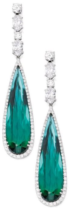 Pair of 18 Karat White Gold, Green Tourmaline and Diamond Pendant-Earrings.   Set with two pear-shaped green tourmalines weighing approximately 31.70 carats, framed and surmounted by numerous round diamonds weighing approximately 2.85 carats and four oval-shaped diamonds weighing approximately 2.95 carats. Sotheby's.