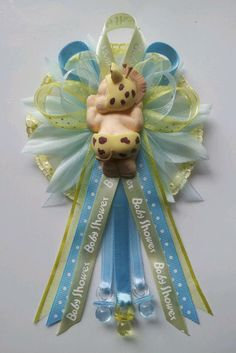 Mommy baby shower corsage with baby wearing giraffe bonnet and diaper centerpiece