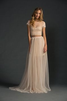 Complemented by beach waves and natural makeup, who thought a crop top wedding dress could be so unfussy? We love the sheer overlay with cap sleeves over the camisole.