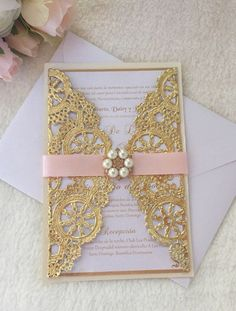 Double Layered invitation printed on a delicate pearlescent white cardstock and backed on ivory pearlescent cardstock wrapped with a beautiful gold metallic doily and topped with a blush pink fabric ribbon and gold pearl and rhinestone brooch.  This invitation can be modified for any theme/occasion such as wedding, baptism, baby shower, sweet sixteen, birthday etc. just state all your options during check out or convo us.  Each invitation is $6.00  WHATS…