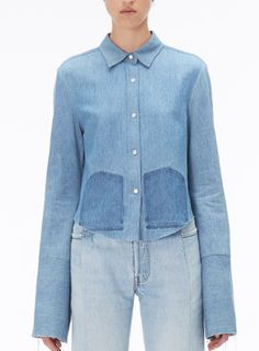 Shop now. The Vogue Edit. Vetements Long-Sleeve Denim Shirt. Typifying Vetements' unique aesthetic, this denim shirt has faded pocket patches and an elongated sleeve. Cut in the label's distinctive cropped fit that sits on the waist, it features a longer back hem and unfinished cuffs.