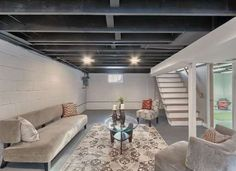 11 Doable Ways to DIY a Basement Ceiling - Charcoal-colored rafters may seem like an unexpected choice for a basement ceiling, but when you con... - Zillow Digs home in Brentwood, MO