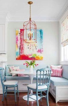Ein kleiner runder weißer Tisch entspricht einer hellblauen gepolsterten Bank und Stühlen