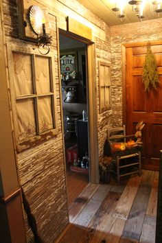 Primitive foyer..barn wood floor and walls..old windows were hung on the wall like a picture with old pillow cases to look like a curtain..and 2 of the windows have feed sacks behind them to look like a curtain