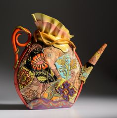"""This hand built ceramic piece uses a unique process where I press antique and contemporary textures into clay. The surface is hand painted with thinned out colored clay which allows for color to be imbedded in the surface. Another layer of color is added through the use of various glazes.The ceramic ruffle top and spiral handle adds color and playfulness to this French inspired piece.Dimensions of ceramic vesselHeight 21"""" at furthest point,  Width 21"""" approximate, ..."""