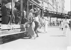 Slice of life! A mother helps her child off the trolley on a Broadway in New York City, July, 1913