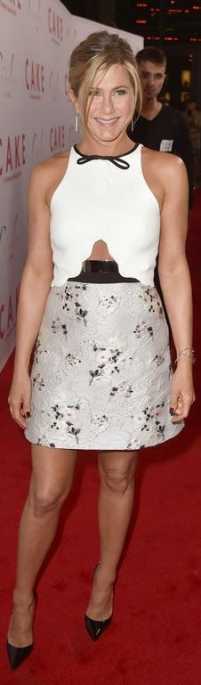 Who made Jennifer Aniston's white scallop bow top, floral gray skirt, jewelry, and black patent pumps?