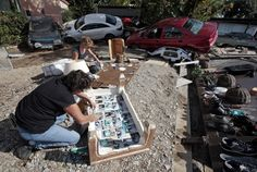 Women place family pictures out to dry, saved from their home, near cars that were damaged after flooding caused by torrential rain in Biot, France, October 4, 2015. Flooding along part of the French Riviera has killed at least 16 people, officials said Sunday. The downpour hit the Alpes-Maritimes region, which lies at the eastern end of France's Mediterranean coast and borders Italy, on Saturday evening. REUTERS/Eric Gaillard