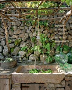 outdoor kitchen, love the stone and trellis roofing -Stone sink Cote Sud magazine