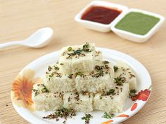 Rava Dhokla             1 cup Fine Rava (sooji / semolina) 1 cup Sour Curd 1/3 cup Water 1 teaspoon Eno 1 teaspoon + 1 teaspoon Cooking Oil Salt For Tempering: 1 tablespoon Oil 1/2 teaspoon Mustard seeds 1/2 teaspoon Cumin seeds 1/2 teaspoon Sesame Seeds (til) 1 small Green Chilli, deseeded and finely chopped 4 to 5 Curry Leaves 1 tablespoon finely chopped Fresh Coriander Leaves