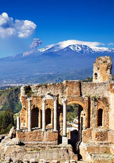 Ruins of the Greek Roman Theater with Etna erupting, Taormina, Sicily, Italy…