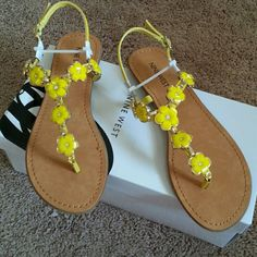 New in Box Nine West Flower Design Sandals Brand New Nine West Yellow Flower Design Sandals.  Beautiful Gold-tone Accents. A little thread is showing in photo 3 but was bought that way and is secure so no worries. Little Rhinestones in each Flower.  I have these in white and love them. Just don't wear much yellow. Nine West Shoes Sandals