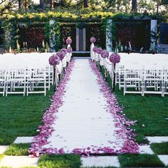 Coat the edge of your aisle runner in bright petals, and place coordinating pomander balls on the chairs.