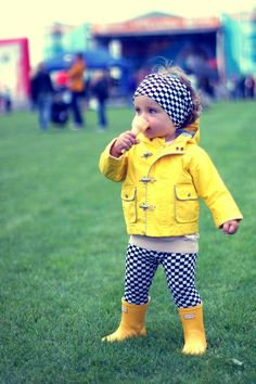 An Adorable little girl in checkered headband, yellow jacket, checkered leggings and yellow gumboots eating ice-cream.