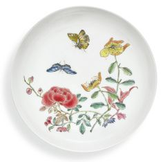 A RUBY-BACK FAMILLE-ROSE DISH QING DYNASTY, 18TH CENTURY thinly potted with an eggshell body, the shallow rounded sides resting on a tapered foot, brightly painted to the interior with two butterflies hovering amongst a rose, an aster and various other flowers and leafy sprays, the exterior applied with a mottled ruby-pink glaze stopping neatly at the foot, the base reserved in white