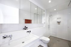 All white bathroom with contrasting grey floors.  Residence in Surry Hills (warehouse conversion) by Smart Design Studio.