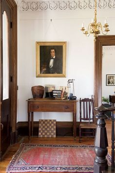 A portrait of the original owner hangs in the hallway. (Photo Credit: Patricia Lyons) Love table and rug.
