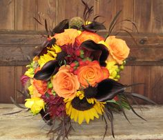 Fall wedding bouquet of sunflowers, callas, dahlias, freesia and roses.