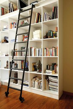 A spray-painted roller ladder allows access to the upper compartments of the built-in floor-to-ceiling shelves.