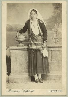 Studio portrait of a woman wearing a folk costume, © The Austrian Museum of Folk Life and Folk Art. Full-length shot of a woman wearing a dark skirt, an embroidered jacket and a light-coloured shawl as a headdress. Comment:	Most probably produced for commercial use. Probably a Christian folk dress. At the time, Kotor was part of the Austrian-Hungarian Monarchy. Nowadays it is in Montenegro.