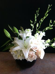 Colombian Roses, Hydrangea, Cymbidium Orchid blooms, Lilies and Dendrobium Orchids designed in a black glass bubble bowl.