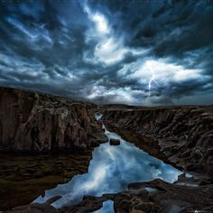 Thunderstorm with lightning strikes over a Lake Superior coastal shelf near Grand Marais, Minnesota. Crevices with pools of water reflect the storm clouds. | by Matt Anderson from NatGeo Yourshot
