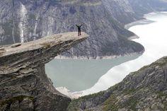 TROLLTUNGA: Nummer fire på listen til Huffington Post som skriver at Trolltunga er perfekt for en «photo op» og blant de mange utrolig vakre stedene i Norge. Her er VG-journalist Mona Langset på tuppen av tunga. FOTO: HALLGEIR VÅGENES / VG