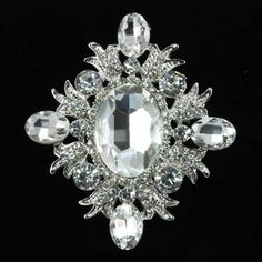 Fashion+brooch+assembled+with+a+loarge+chunky+crystal+rhinestone+in+the+center+and+four+small+oval+crystal+rhinestones+on+each+siee+and+top;+base+plated+in+silver+color;++Size:+width:+2-1/2+inches+x+height+3+inches