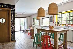 Cocina comedor rústica con aires vintage que combina función y belleza. Destacan la barra tipo banco de madera, grandes lámparas de mimbre y ventanal de vidrio repartido.