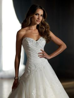 - A line - Lace appliques on tulle skirt - Corset closure - Asymmetrical bodice - Sweetheart neckline with lace and crystal embellishment - Floor length - Chapel train *NOTE* There are no sizes listed