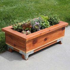 bac à fleurs en bois de design rectangulaire sur quatre pieds en bois et métal et avec un arrangement de plantes succulentes
