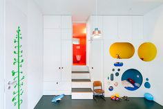 On the apartment's lowest level is the bedroom shared by Mr. Ebers' sons, ages 3 and 1. Built-in storage units in white provide a visual contract with capsule beds lined in bright primary colors. The green tree on the back of the door measures the boys' growth.