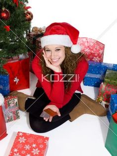 portrait of a smiling young woman wearing santa hat. - Portrait of a smiling young woman wearing Santa hat while sitting next to Christmas tree, Model: Brittany Beaudoin