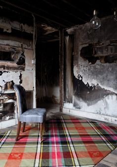 Vivienne Westwood Rug Company.  The pairing of the plaid rug and rustic walls give this room a non-traditional cozy.