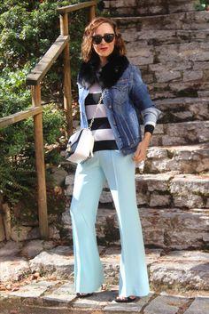 Pantalones en azul y sandalias en negro y melena midi y ondas y cuello de piel y jersey de rayas en blanco y negro y el bolso a juego chaqueta vaquera