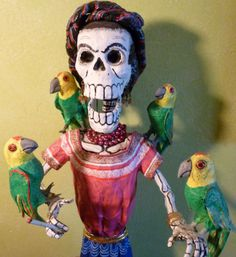 "This striking sculpture was made by Miguel Linares of the famous Mexico City family which has made the art form of ""cartonería"" (papier-mâché) internationally famous. Historical figures, characters from cartoons and folklore, even the themes of Frida Kahlo's paintings are translated into cartoneria sculptures. These figures are usually depicted as calaveras (skeletons) which, representing the ""other"" face of the Mexican lifecycle, are as involved in daily life and fiestas as the living."