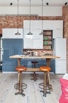 Glossy modern kitchen cabinets stands in contrast to the brick wall backdrop