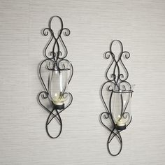 Add a touch of distinction to your room decor with our classic wall sconces.  A beautiful extension of black twisted wrought iron, each sconce has a glass hurricane suitable for a tea light or votive candle. Candles not included