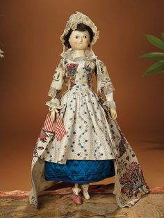 """18th century woorden doll, wearing original costume including blue silk quilted petticoat, separate coin pockets, hand-stitched stays, three undergarments, blouse with embroidered collar, ruffled bonnet, apron, transfer-printed robe with exotic bird design, and an early ink-script paper note indicating """"this doll belonged to Mary Wilson, Tranby Croft 1772""""."""