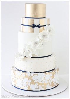 Golden Glamour - four-tiered white wedding cake with the lower half of each tier…