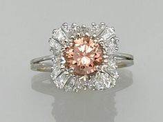 A natural fancy colored diamond and eighteen karat white gold ring  of ballerina design, centering a brown-orange round brilliant-cut diamond weighing 1.17 carats, surrounded by tapered baguette-cut diamonds; estimated total diamond weight: 1.50 carats.