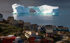 An iceberg floats near a harbour in the town of Kulusuk, east Greenland...