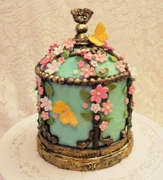 Victorian Bird Cage - Strawberry cake with white chocolate/strawberry buttercream filling and frosted with regular buttercream.  The modeling chocolate decor was brushed with gold to get the metal look.  Gum paste flowers and butterflies.